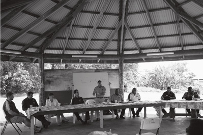 A photograph showing community consultation, Ugar Island