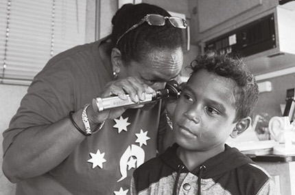 A photograph of a local medical practitioner performing health check on a boy