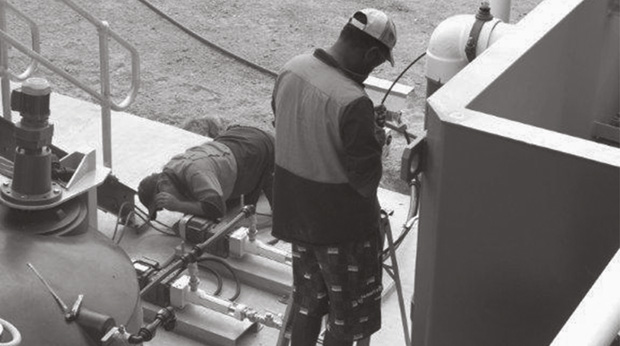 A photograph showing two men working at a plant