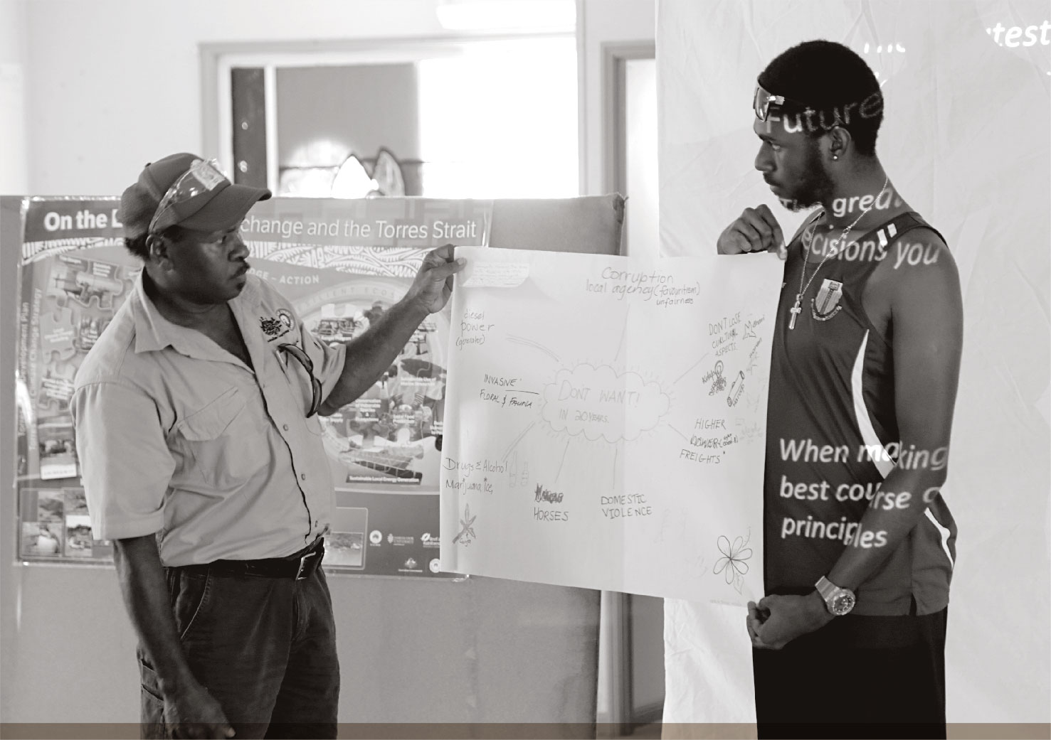 a photograph of TSRA RANGER JOHN WIGNESS AND A COMMUNITY MEMBER AT A CLIMATE CHANGE WORKSHOP IN KUBIN.