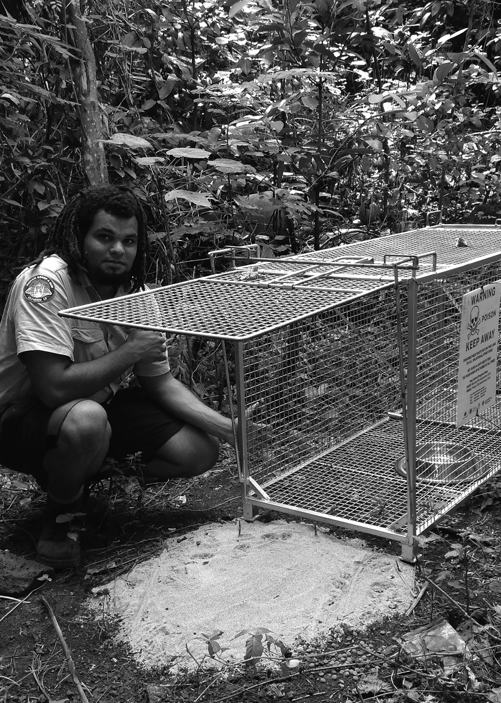 a photograph of Mer Ranger Aaron Bon inspecting a dog trap for turtle protection