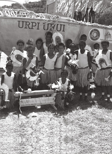 A photograph showing children gathered in front of a ranger boat during the blessing